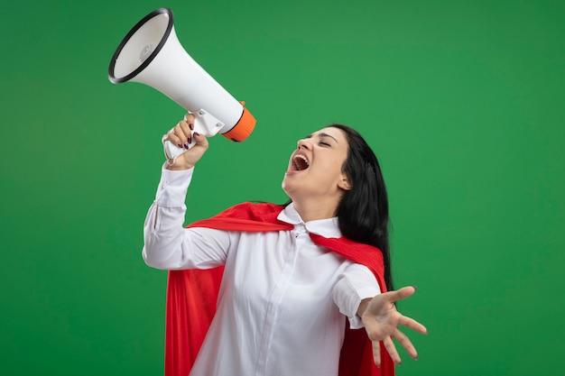 Счастливая и сумасшедшая молодая суперженщина, стоящая в профиле, кричит в громкоговоритель с закрытыми глазами, изолирована на зеленой стене