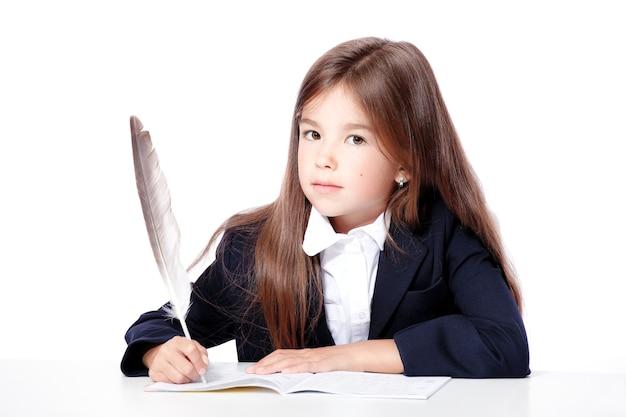 Счастливая и милая школьница-подросток пишет в книге или тетради