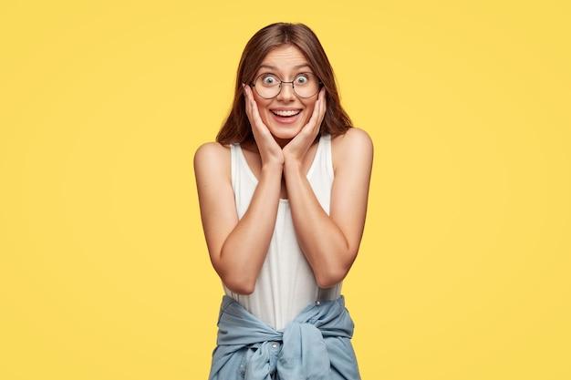 Счастливая и довольная молодая брюнетка в очках позирует на желтой стене