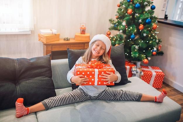 Счастливая и мечтательная девушка сидит на диване в шпагате и держит в руках подарок. она улыбается. девушка очень позитивная.