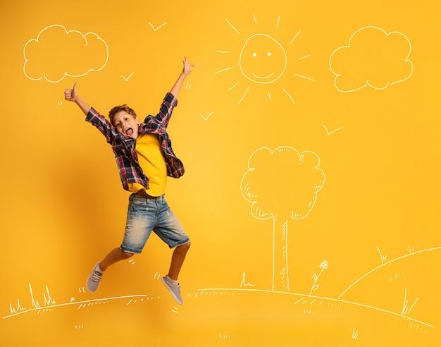 Счастливый и эмоциональный ребенок прыгает через желтый фон.