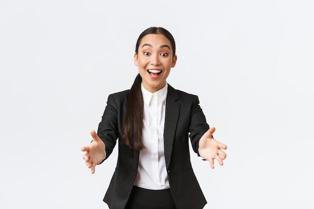 Счастливая и взволнованная азиатская женщина-предприниматель протягивает руку, чтобы поздравить коллегу с удивительным достижением, наклоняется для объятий или объятий, впечатлена большим количеством вещей, белый фон