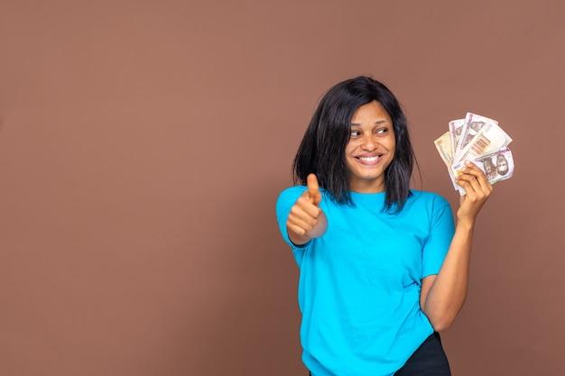 한 손에 돈을 들고 엄지손가락을 치켜드는 행복하고 흥분된 아름다운 아프리카 여성