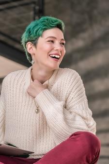 嬉しくてワクワク。幸せと興奮を感じながら大きく笑う美しい緑の髪の女性