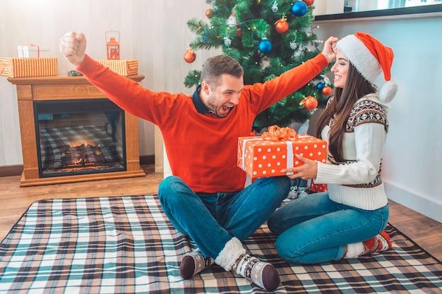 幸せと興奮の男は指を交差して毛布の上に座っているし、手を伸ばす