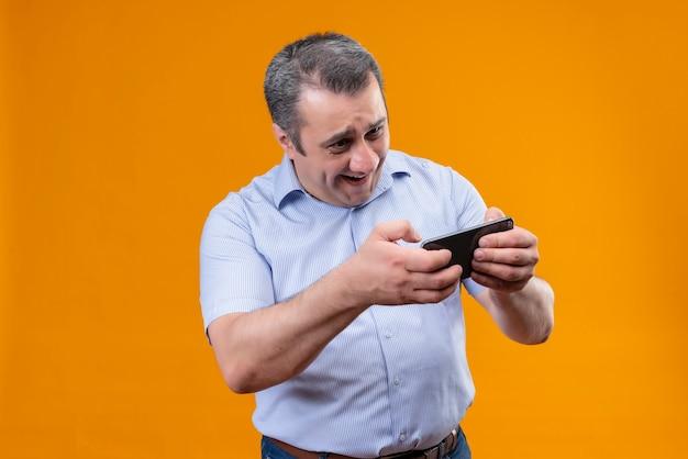 Счастливый и взволнованный мужчина среднего возраста в синей вертикальной полосатой рубашке играет в игру на своем мобильном телефоне, стоя