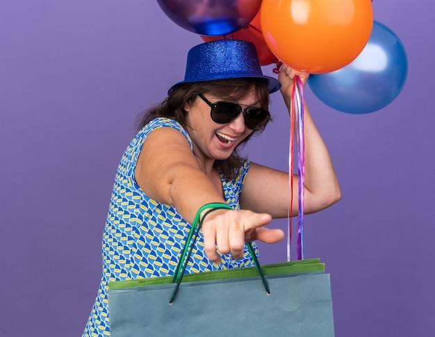 紫色の壁の上に立って誕生日パーティーを祝うギフトでカラフルな風船と紙袋の束を保持しているパーティー ハットとメガネで幸せで興奮した中年女性