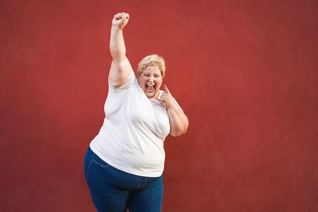 행복하고 흥분된 더하기 크기 여자 성공 축하하고 제스처를 승리