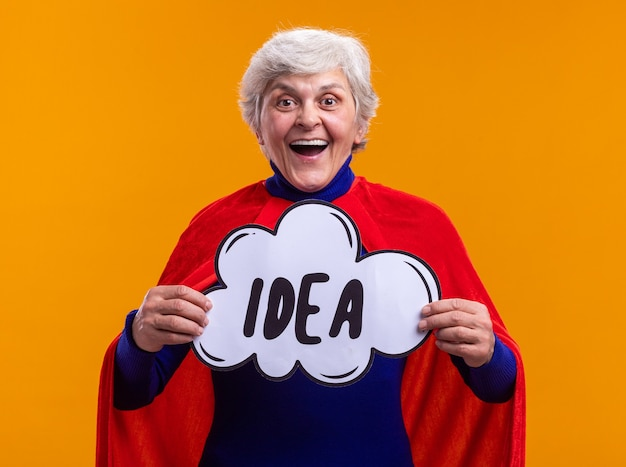 幸せで興奮した年配の女性のスーパーヒーローは、オレンジ色の背景の上に元気に立って笑顔のカメラを見て単語のアイデアと吹き出しサインを保持している赤い岬を身に着けています