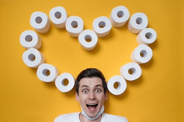 笑顔のトイレットペーパーの心に囲まれた黄色の背景に幸せで興奮した若い男