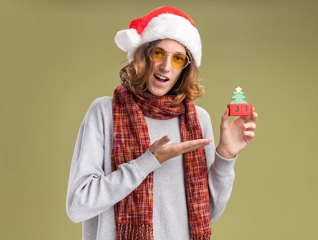 녹색 벽 위에 서있는 새해 날짜와 장난감 큐브를 제시하는 그의 목 주위에 따뜻한 스카프와 함께 크리스마스 산타 모자와 노란색 안경을 쓰고 행복하고 흥분된 젊은 남자