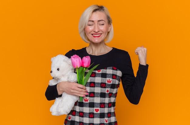 オレンジ色の壁の上に立って国際女性の日を祝う拳を握り締める贈り物としてチューリップとテディベアの花束を保持している美しいドレスで幸せで興奮した若い女性