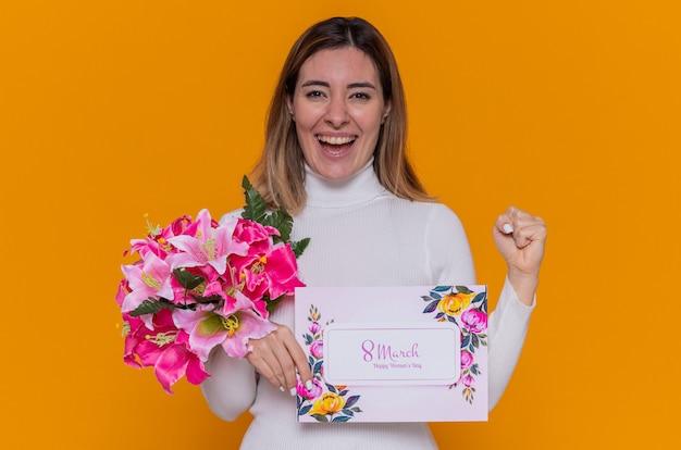 인사말 카드와 꽃의 꽃다발을 들고 흰색 터틀넥에 행복하고 흥분된 젊은 여자