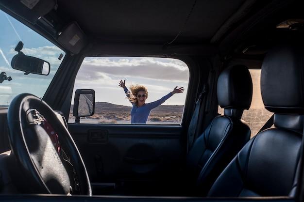 幸せで無料の代替冒険旅行観光客の女性は、屋外の山と野生の砂漠を背景に車の外で楽しんでいます-大人の女性は車で旅行旅行の休暇を楽しんでいます Premium写真