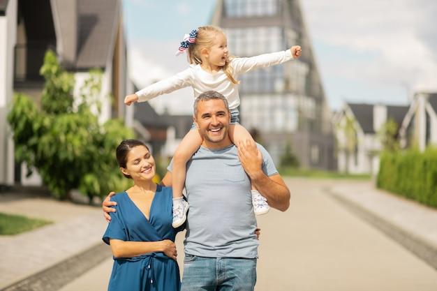 Счастливы и свободны. очаровательная милая дочка чувствует себя по-настоящему счастливой и свободной на семейной прогулке
