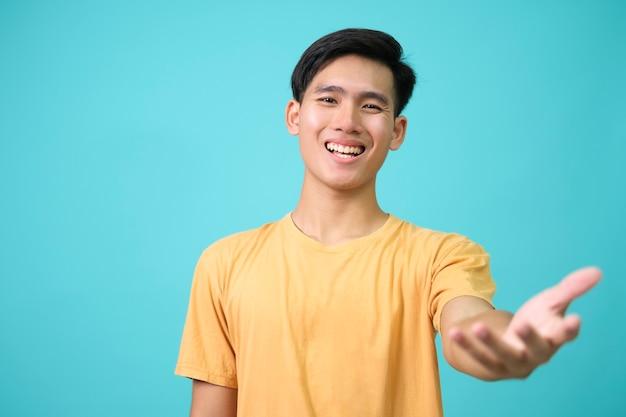 幸せでフレンドリーな男は、親愛なるゲストに温かい歓迎の抱擁を与え、抱きしめるか抱擁で手を広げ、愛を込めて挨拶する人を笑顔にし、青い背景に立っています。