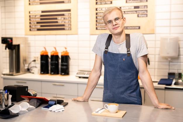 Счастливый и дружелюбный молодой бариста в фартуке и футболке смотрит на вас, стоя у стойки в кафетерии