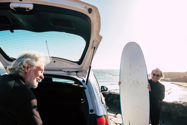 해변에 가기 위해 차에서 서핑 테이블을 준비하는 행복하고 재미있는 노인 부부 - 야외 활동을 하는 활동적인 성숙한 사람들