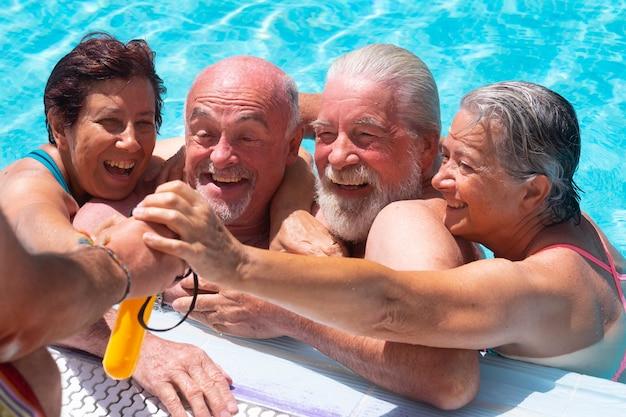 Счастливая и веселая группа пожилых людей в бассейне, наслаждаясь летом и выходом на пенсию