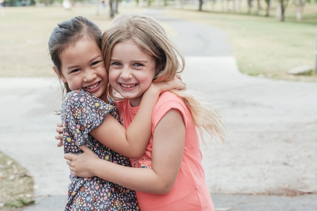 Счастливые и здоровые смешанные расы молодые маленькие девочки обнимаются и улыбаются в парке, лучший друг дети и дети дружба концепция
