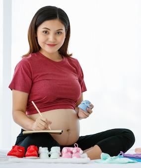 Концепция счастливой и здоровой матери. азиатская беременная женщина сидит на кровати, держа книгу и карандаш, улыбаясь и глядя на милую красную детскую обувь с полной любовью.