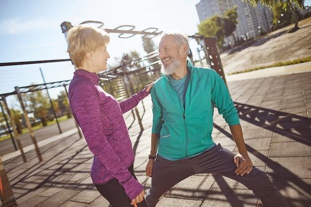 야외에서 함께 체조를 하는 운동복을 입은 행복하고 건강한 웃는 성숙한 가족 커플