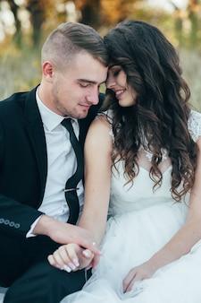Счастливые и влюбленные невеста и жених в осеннем парке в день свадьбы