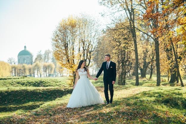 행복하고 사랑에 빠진 신부와 신랑은 결혼식 날 가을 공원에서 산책