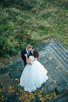 Счастливые и влюбленные невеста и жених гуляют в осеннем парке в день свадьбы