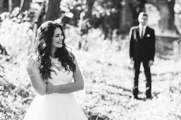 幸せと恋に新郎新婦が結婚式の日に秋の公園を歩く