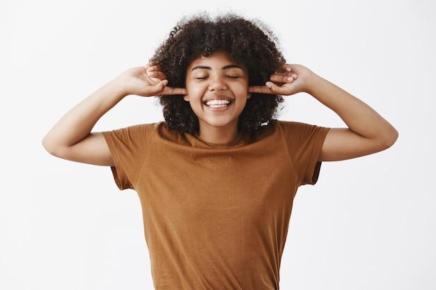 人差し指で大きく笑って目を閉じて沈黙を楽しんでいる耳を覆うトレンディな茶色のtシャツのアフロの髪型を持つ幸せで楽しい感情的なアフリカ系アメリカ人女性