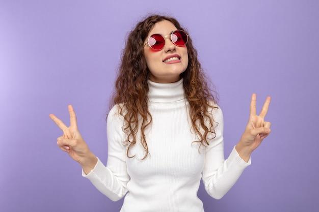 紫の上に元気に立って笑顔のvサインを示す赤い眼鏡をかけている白いタートルネックの幸せで楽しい若い美しい女性