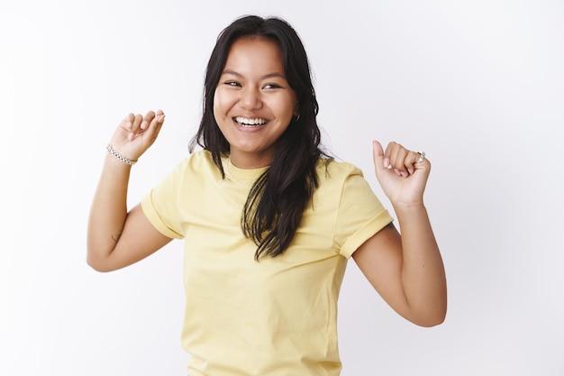 행복하고 즐거운 젊은 근심 없는 여성이 손을 들고 음악 리듬을 옆으로 바라보고 활짝 웃으며 멋진 하루를 즐기고 있는 프로젝트의 끝을 축하하면서 승리의 춤을 추고 있습니다.