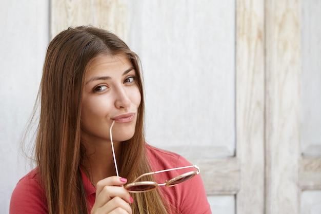 Счастливая и радостная молодая кавказская женщина с длинными волосами, надувает губы, держит тени и касается губ кончиком виска, флиртует и загадочно смотрит, позирует изолированно у деревянной стены