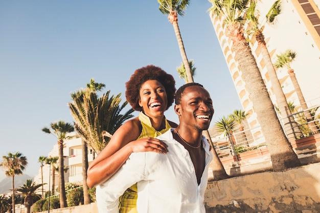 Счастливая и смеющаяся пара в игривой деятельности вместе на открытом воздухе в тропическом месте улыбается и радостная концепция для разнообразия расы чернокожих мужчина и женщина веселые люди в радости снаружи несут