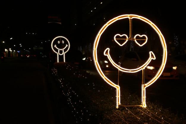 밤에 길가에 행복하고 사랑하는 얼굴 모양의 네온 사인