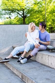 Счастливая и любящая пара подростков в скейтпарке