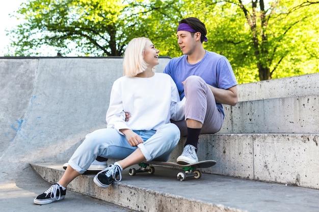Счастливая и любящая пара подростков в скейт-парке