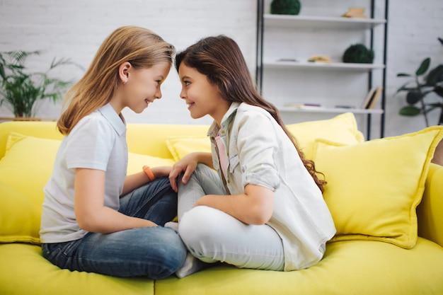 행복하고 기뻐하는 여자는 얼굴을 맞대고 소파에 앉아있다. 그들은 서로의 눈을보고 웃습니다. 십대들은 다리를 계속 교차시킵니다.
