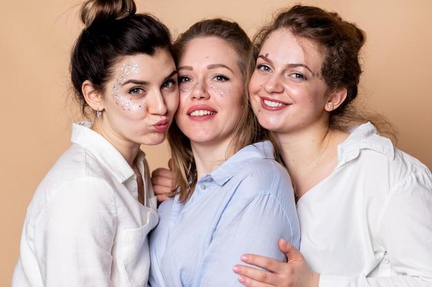 Счастливые и полные многокультурные женщины в бюстгальтерах, изолированных на бежевом. разнообразная красота. три многонациональных дамы, завернутые в банные полотенца, позируют, улыбаясь на бежевой стене.