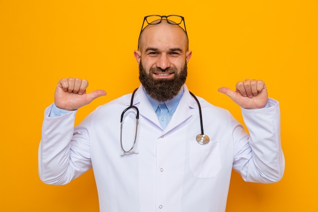 オレンジ色の背景の上に立っている彼の頭に眼鏡をかけた首の周りに聴診器を備えた白衣を着た幸せで喜んでいるひげを生やした男の医者