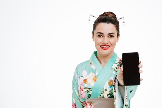 흰색에 스마트폰을 보여주는 전통적인 일본 기모노를 입은 행복하고 기쁘게 생각하는 여자