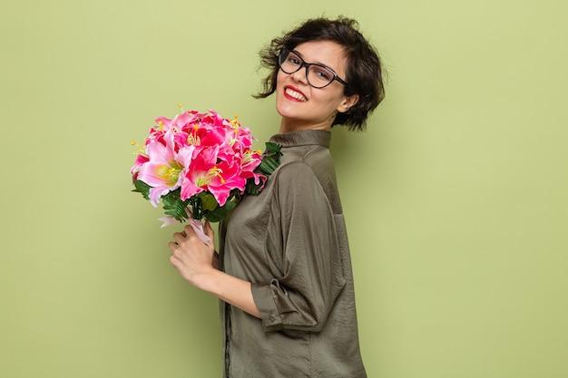 Счастливая и довольная женщина с короткими волосами, держащая букет цветов, глядя в камеру, весело улыбаясь, празднует международный женский день 8 марта, стоя на зеленом фоне