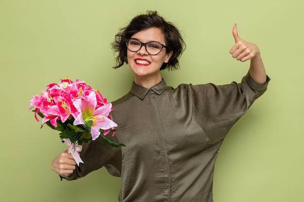 Счастливая и довольная женщина с короткими волосами, держащая букет цветов, глядя в камеру, весело улыбаясь, показывает палец вверх, празднуя международный женский день 8 марта, стоя на зеленом фоне