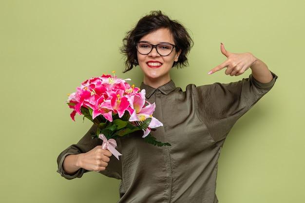 Счастливая и довольная женщина с короткими волосами держит букет цветов, указывая на нее указательным пальцем, весело улыбаясь, празднует международный женский день 8 марта, стоя на зеленом фоне