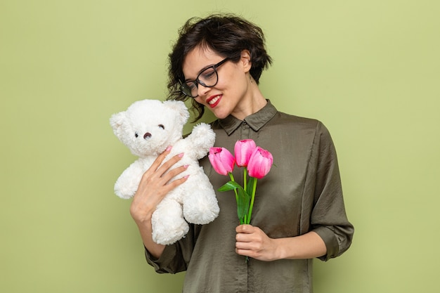 緑の背景の上に立って国際女性の日3月8日を祝って元気に笑っているチューリップとテディベアの花束を保持している短い髪の幸せで幸せな女性