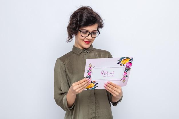 흰색 배경 위에 서 있는 3월 8일 국제 여성의 날을 축하하는 얼굴에 미소를 지으며 인사말 카드를 들고 있는 짧은 머리를 가진 행복하고 행복한 여성