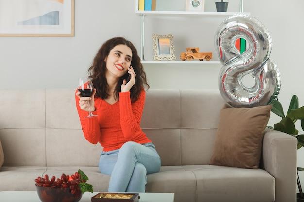 3月8日国際女性の日を祝う明るいリビングルームで携帯電話で話しているワインのグラスとソファに座って元気に笑ってカジュアルな服を着て幸せで喜んでいる若い女性