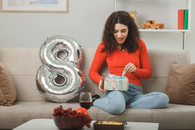 国際女性の日3月8日を祝ってそれを開くためにプレゼントを保持している8番の形をした風船でソファに座って元気に笑ってカジュアルな服を着た幸せで喜んでいる若い女性
