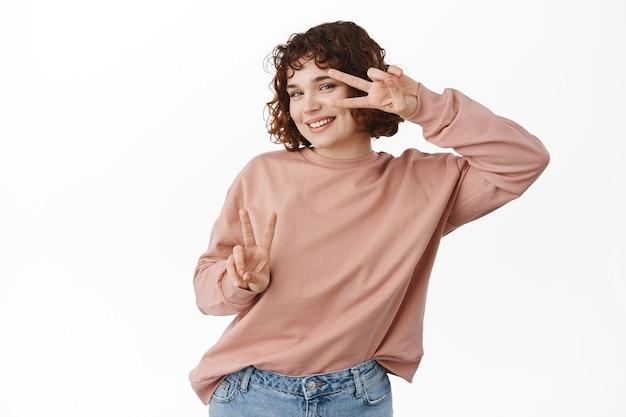 幸せで前向きな白人の女の子、かわいいピースのサインで踊り、陽気に見え、白のカジュアルな服を着て立っています